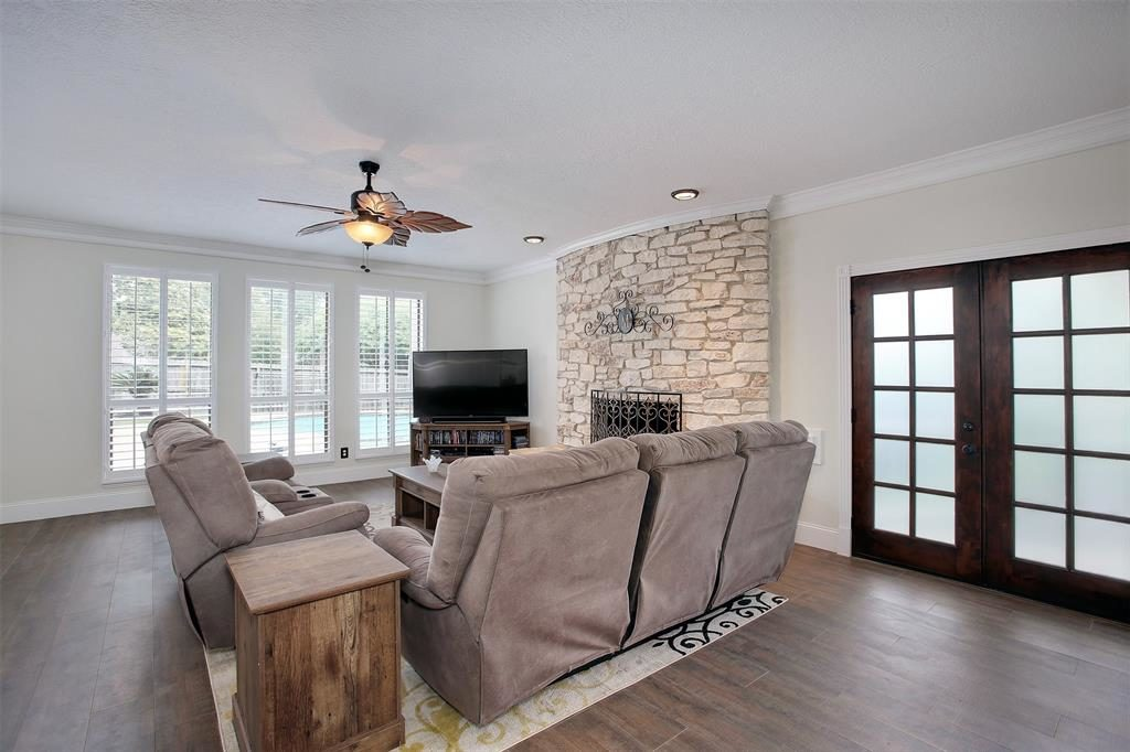 curved stone fireplace living area french doors to pool